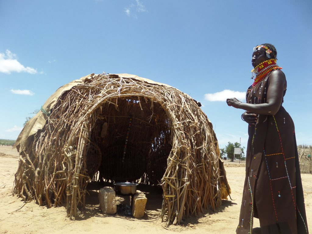 turkana lady standing outsie a traditional kitchen