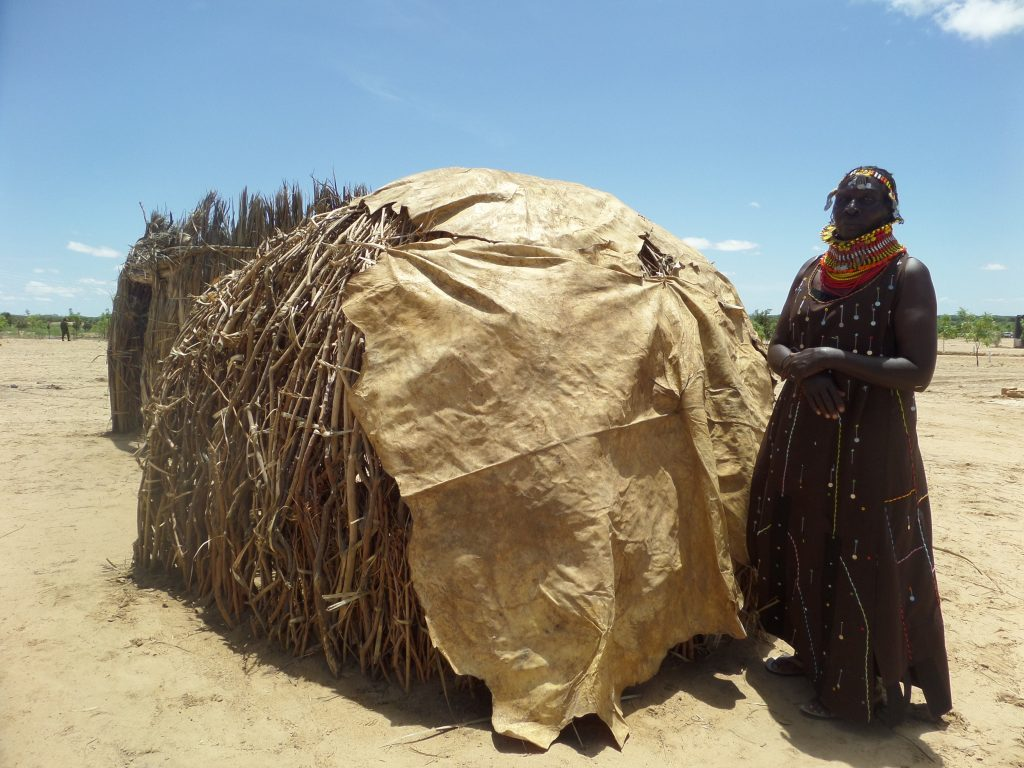 turkana woman standing outside a hut