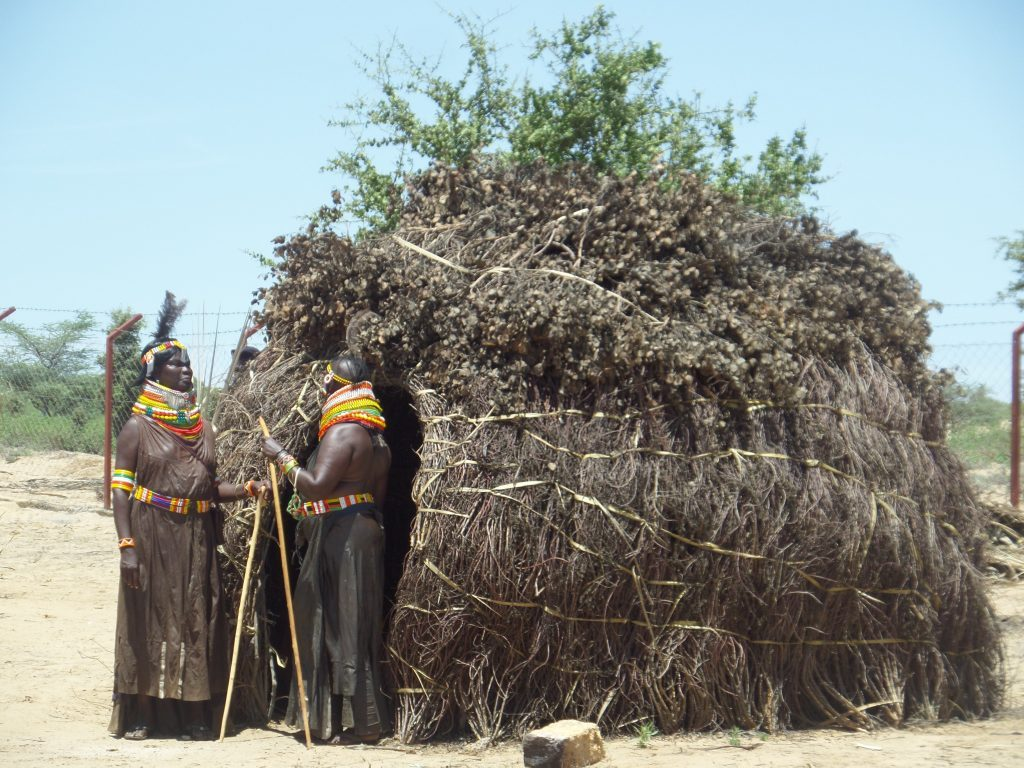 turkana women standing outside a hut